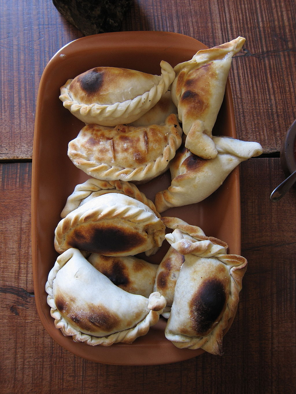 1024px-Empanadas_salteñas_By travelwayoflife [CC BY-SA 2.0 (httpcreativecommons.orglicensesby-sa2.0)], via Wikimedia Commons